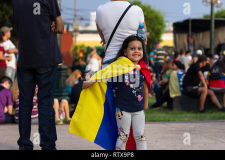 Lima, Peru - February 2 2019: Adorable cute little girl playing with Venezuelan flag at protest against Nicolas Maduro in support of Juan Guaido - Stock Photo