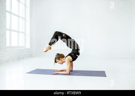 Young woman keeping pose, practising yoga in the white studio - Stock Photo