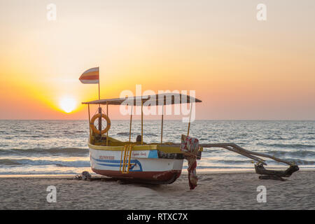 A dolphin cruise boat on the beach of Agonda in India at sunset - Stock Photo