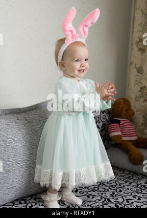 funny little girl in a headband with bunny ears claps her hands and laughs - Stock Photo