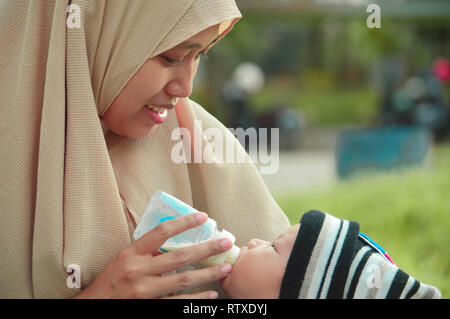 closeup portrait of beautifull baby boy drinking milk from his muslim mother from feeding bottle - Stock Photo