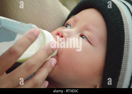 closeup portrait of beautifull baby boy drinking milk from his mother from feeding bottle - Stock Photo