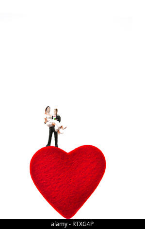 married couple, miniature figurine standing on a heart shape, love and marriage concept - Stock Photo