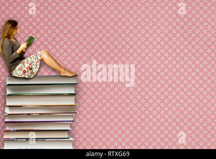 teen girl sitting on a pile of books and reading - Stock Photo