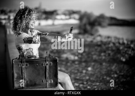 Black and white travel and vacation concept with beautiful hyoung curly woman taking selfie picture - old vintage luggage hand bag near her - defocuse