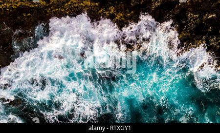 Aerial view to ocean waves. Blue water background - top vertical view of coastline and big power waves on the rocks - splash and dangerous concept for - Stock Photo