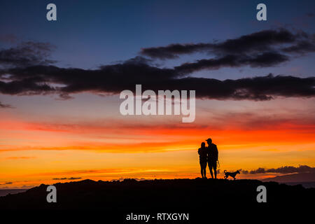 Romantic couple wioth dog enjoying and looking the sunset with red and orange coloured clouds in the sky - wanderlust and travel concept for happy peo - Stock Photo
