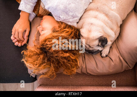 Love and protection and best friends forever concept with beautiful caucasian woman sleeping near her lovely puppy dog pug - friendship from top verti - Stock Photo