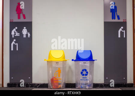 Picture for your concept  yellow trash is general waste and blue is recyclable waste in front of the bathroom inside the airport building. - Stock Photo