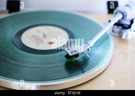 A clear vinyl long playing record on a turntable with a needle arm on the record track playing - Stock Photo