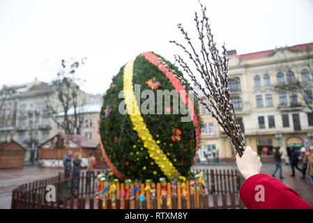 woman holding branch on willow in front of big decoration easter egg - Stock Photo