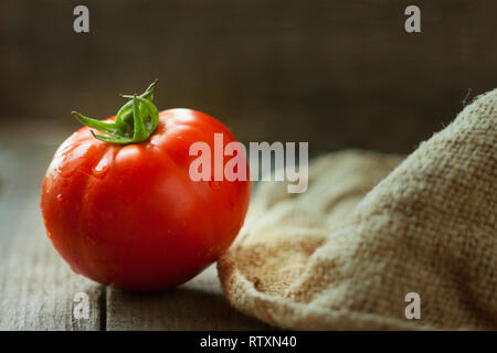 one tomato on a wooden table with sackcloth - Stock Photo