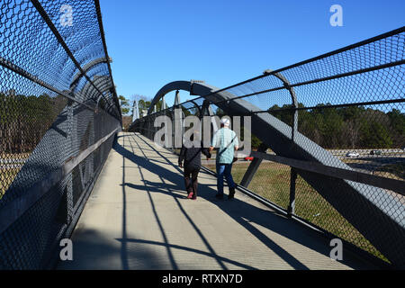 A couple crosses the Reedy Creek Trail pedestrian bridge over the 440 interstate in Raleigh North Carolina. - Stock Photo