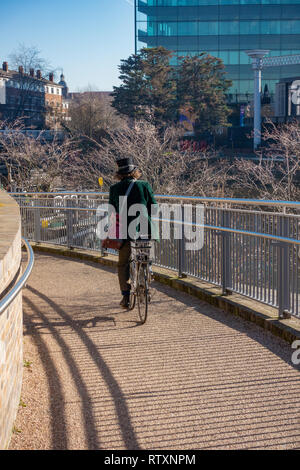 Eccentrically dressed man wearing a Top Hat and wearing a Green Velvet Jacket riding a pushbike at Coal Drops Yard, Kings Cross, London, England. - Stock Photo