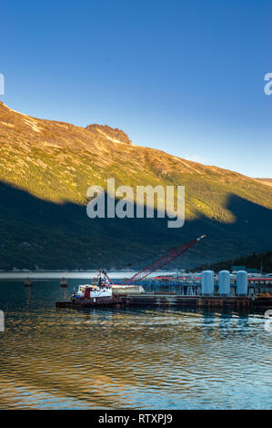 September 15, 2018 - Skagway, AK: Broadway Dock industrial cargo wharf with tugboat and crane at sunrise. - Stock Photo