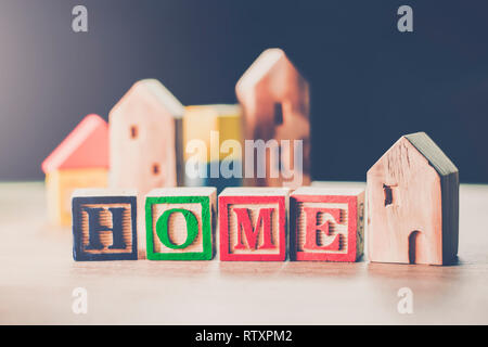 Home wooden toy model, Miniature houses for loan purchase concept building blocks arranged in row background - Stock Photo