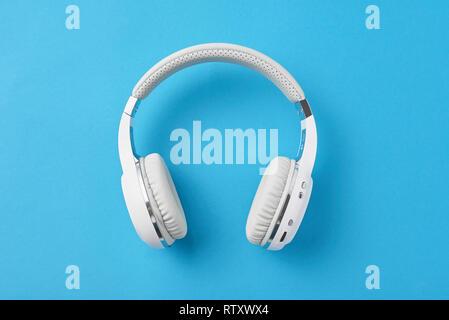 White wireless headphones on pastel blue background - Stock Photo