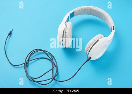 White headphones on pastel blue background - Stock Photo