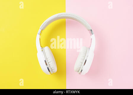 White wireless headphones on pink and yellow background - Stock Photo