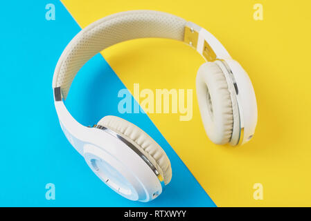 White wireless headphones on blue and yellow background - Stock Photo