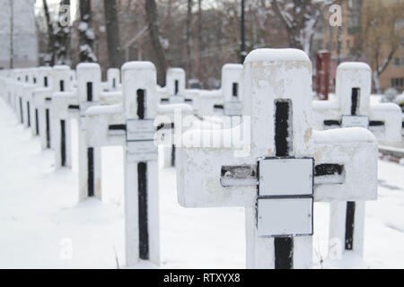 Close-up white crosses on the graves of warriors at cemetery. - Stock Photo