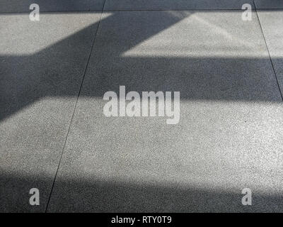 Shadows from morning sun on concrete airport waiting hall floor. Abstract natural light vs artificial material background. - Stock Photo