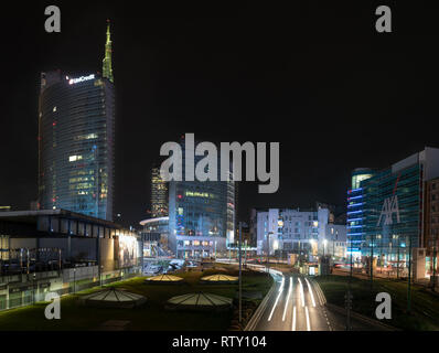 03/02/2019 Mialn, Italy: Unicredit tower, Gae Aulenti square, financial district of milan seen from the overpass Bussa. Nocturnal scene with light tra - Stock Photo