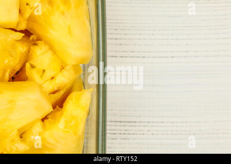 Tabletop view, detail - yellow pineapple cut in pieces, in square glass bowl, white boards desk / space for text on right. - Stock Photo