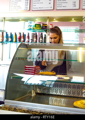A young waitress in an ice cream parlour in North Yorkshire England carefully cutting a slice of home-made apple pie - Stock Photo