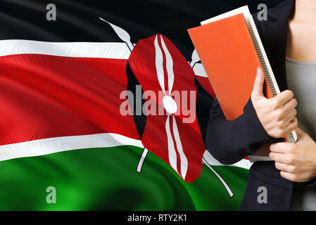 Learning Kenyan language concept. Young woman standing with the Kenya flag in the background. Teacher holding books, orange blank book cover. - Stock Photo