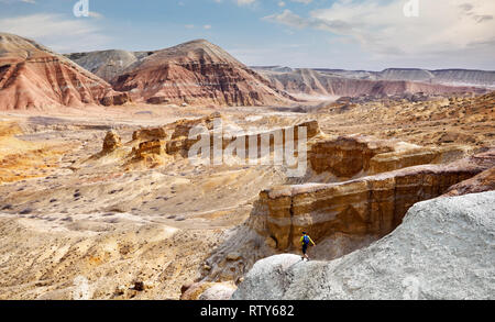 Tourist walking at the trail on surreal yellow mountains in desert park Altyn Emel in Kazakhstan - Stock Photo