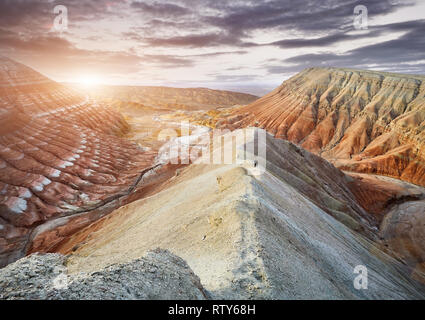 Tourist walking at the trail on surreal yellow mountains at sunset in desert park Altyn Emel in Kazakhstan - Stock Photo