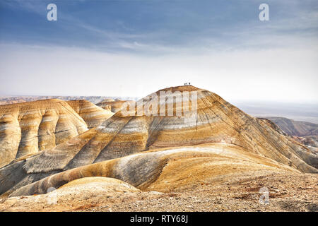 Tourist silhouettes on the top of surreal yellow mountain in desert park Altyn Emel in Kazakhstan - Stock Photo