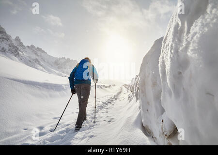Tourist with blue backpack walking on the snow road in the mountains at snowfall - Stock Photo