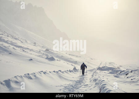 Tourist on the snow road in the beautiful mountains at winter - Stock Photo