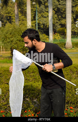 Young man entomologist collecting insects using an insect net or swiping net for his insect specimen collection during a bright summer - Stock Photo