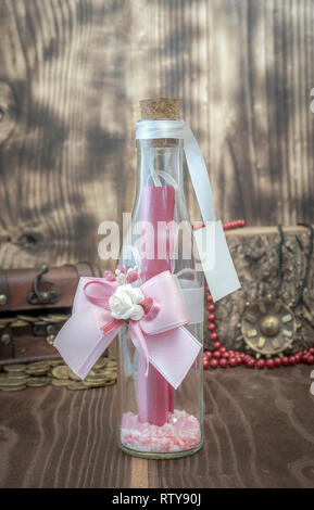 Bottle decorated with greasy and flower with message behind a chest with treasure pearls and medallion - Stock Photo