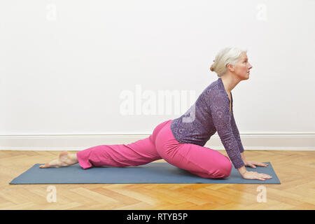 Senior woman with gray hair exercising yoga at home on a mat in front of a white wall, asana pigeon intro - Stock Photo