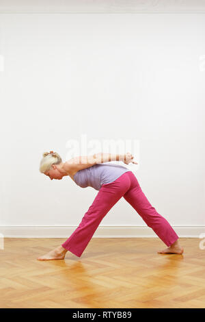 Senior woman with gray hair doing yoga exercise at home in front of a white wall, pose pyramid, copy space - Stock Photo