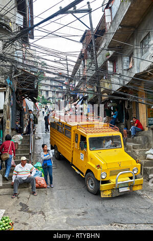 Baguio City, Benguet Province, Philippines - May 5, 2012: High-angle view of a yellow colored jeepney at a steep street in a wet market area - Stock Photo