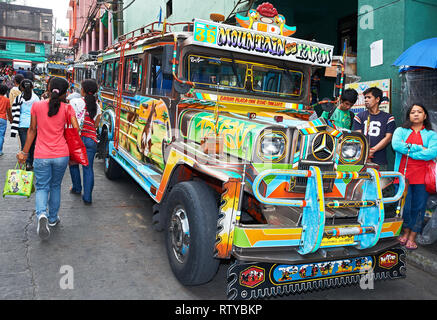 Baguio City, Benguet Province, Philippines - May 5, 2012: Front low-angle view of colorful jeepneys parking at a steep street in downtown area - Stock Photo