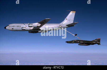USAF United States Air Force Boeing KC-135E Stratotanker with MCDonnell Douglas F-4E Phantom II while air refueling - Stock Photo