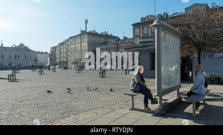 People studying a map at the metal chairs in memory of the jewish people killed on the Ghetto Heroes Square, Krakow, Poland - Stock Photo