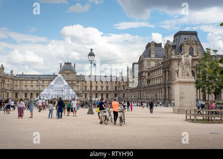 Paris, France - 06/25/2016: tourists visiting the Louvre, Pyramid covered in ephemeral artwork by JR 'unframed' project - Stock Photo