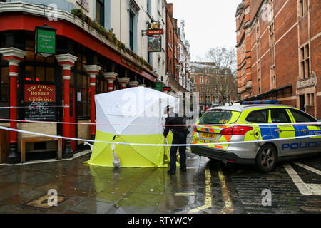 Soho, London, UK. 3rd Mar 2019 - A forensic officer at the crime scene outside The Coach and Horses pub in Romilly Street in Soho. According to the police, a man aged 30 yrs old is seriously injured in hospital and a 40 year old woman has been arrested and remains in custody. Met Police sat that they are linking this stabbing and a stabbing in Camden where a man in his 30s has been arrested on suspicion of attempted murder for the Soho stabbing.   Credit: Dinendra Haria/Alamy Live News - Stock Photo