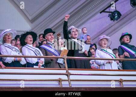 London, UK, 3rd Mar 2019. Women dressed as suffragettes (and a man supporting them) in the audience. March4Women is CARE International's annual month of action for gender equality. This year's London event is held at Central Hall, rather than as an outdoor rally, and features speeches, debate and musical performances from celebrity supporters. Credit: Imageplotter/Alamy Live News - Stock Photo