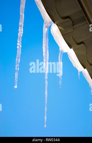 Icicles hanging from the roof in the rays of the sun against the blue clear sky - Stock Photo