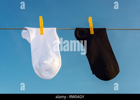 two new, clean, washed white and black socks hang on a rope with yellow clothespins. blue sky background - Stock Photo