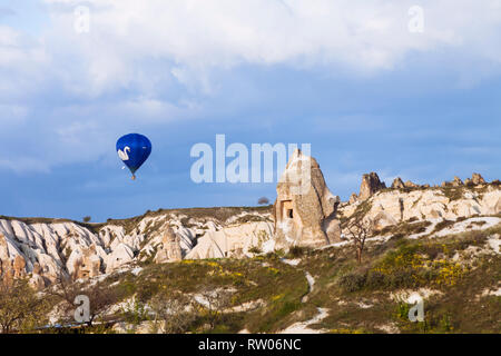 Goreme, Nevsehir Province, Turkey : A hot air balloon flies over fairy chimney rock formations in the historical Cappadocia region. - Stock Photo