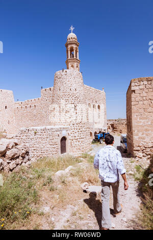 Gülgöze, Mardin province, Turkey : A man walks towards the fortress like Mar Hodtschabo Syriac Orthodox church in Gulgoze or Inwardo, a Syriac village - Stock Photo